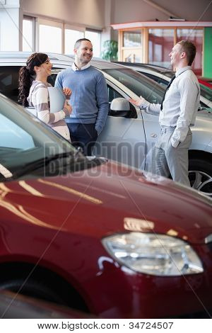 Smiling salesman chatting with customers in a car-shop