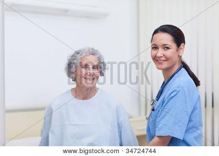 Nurse assisting a patient in hospital ward