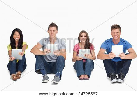 A group of people holding their tablet pc's in their hands as they all look at the camera