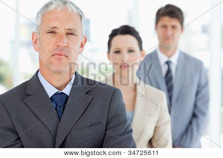 Madura gerente pé na frente de sua equipe séria