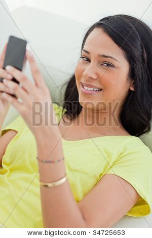 Portrait of a Latino holding her smartphone while lying on a sofa