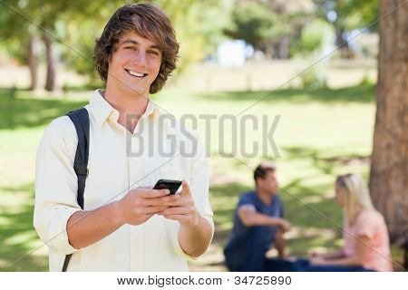 Portrait of a young man holding a smartphone in a park with friends in background
