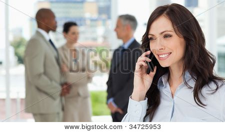 Executive woman talking on the phone in a relaxed way with her team behind her