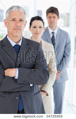 Gerente grave, cruzando os braços na frente de sua equipe de negócios jovem