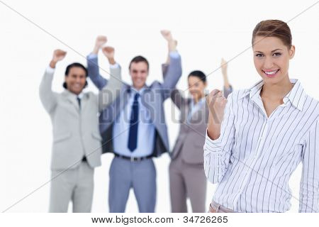 Close-up of a secretary smiling and clenching her fist with enthusiastic business people with their arms raised against white background