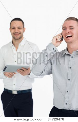 Laughing men with a phone and a tablet computer against a white background