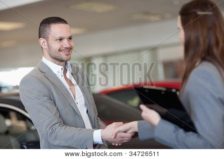 Businesswoman shaking hand of a client in a dealership