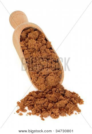 Soft brown sugar in a wooden scoop over white background.