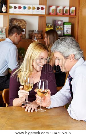 Elderly happy couple sitting with glass of white wine in a caf�?�©