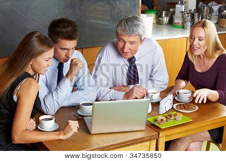 Business people looking at laptop in caf�?�© during a meeting