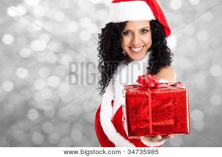 Portrait of a beautiful Christmas girl giving you a gift