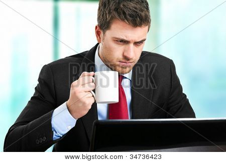 Handsome businessman in his office while drinking some coffee looking at his laptop