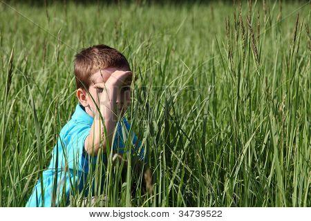 Menino sentado na grama alta