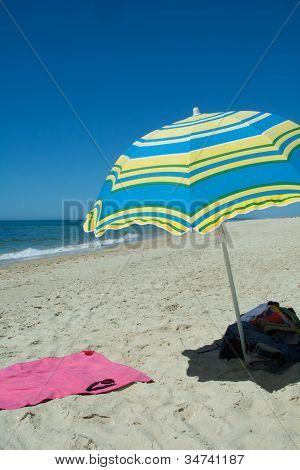 Blue And Yellow Umbrella On A desert Sandy Beach