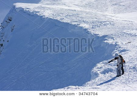 Ski freeriders on the brink of a precipice.