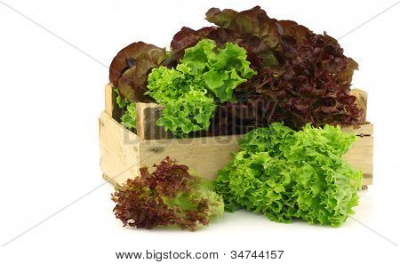 assorted lettuce in a wooden box on a white background