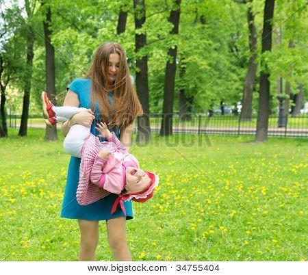 Mother Holding Daughter Head Over Heels