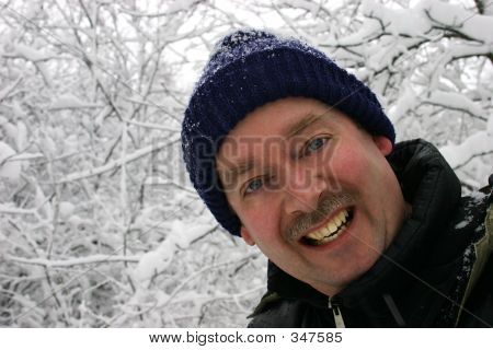 Man Smiling To The Camera While Surrounded By Snow Filled Branch