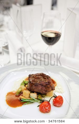 Tenderloin steak with wine on restaurant table