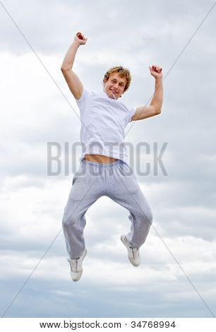 Portrait Of A Happy Young Man Jumping In Air Against Sky.