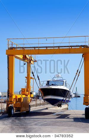 crane travelift lifting a boat on blue sky day in balearic islands