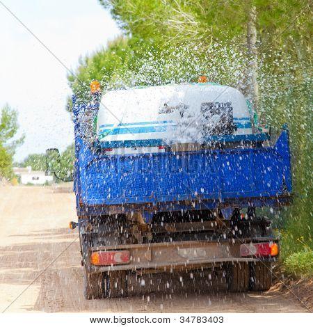 LKW LKW bestreuen Wasser am Sandweg vor Asphalt-Werke zu verbreiten