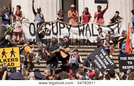 NEW YORK-JULY 11: Occupy Guitarmy protesters rally and play music in front of Federal Hall across from the NY Stock Exchange at the #99MileMarch from Philly to NYC on July 11, 2012 in New York, NY.