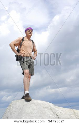 A Mature Male Stands High On A Rock Peak