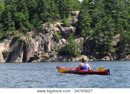 Female Kayaks While Enjoying A Wilderness Lake.