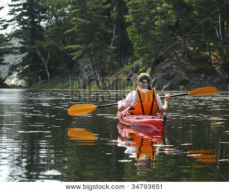 Male Kayaks On A Quiet Lake