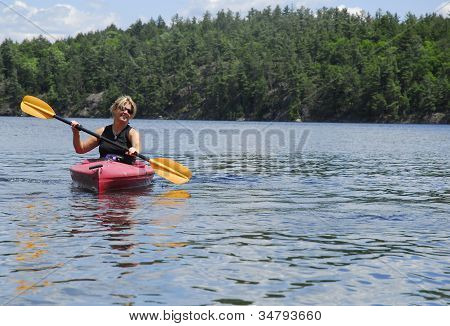 A Female Kayaks Calm Water