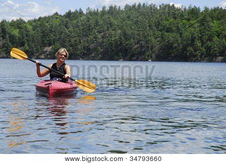 A Female Kayaks Calm Water