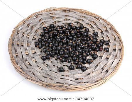 Black currant on wicker mat isolated on white