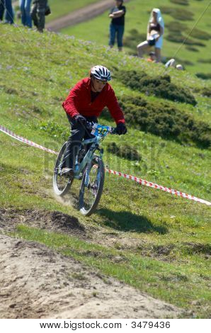 Red Biker On Downhill Race