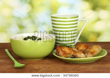 Mashed potato in the bowl and roasted chicken wings in the plate and cup with milk on wooden table close-up
