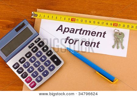 folder with information on apartments for rent on wooden background close-up
