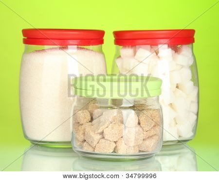 Jars with brown cane sugar lump, white crystal sugar and white lump sugar isolated on white