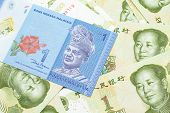 A Close Up Image Of A Blue One Malaysian Ringgit Bank Note On A Bed Of Chinese One Yuan Bank Notes C poster