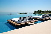 stock photo of infinity pool  - Infinity swimming pool by beach at the modern luxury hotel Pieria Greece - JPG