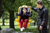 picture of babysitting  - Father pushing disabled boy in special needs handicap swing - JPG