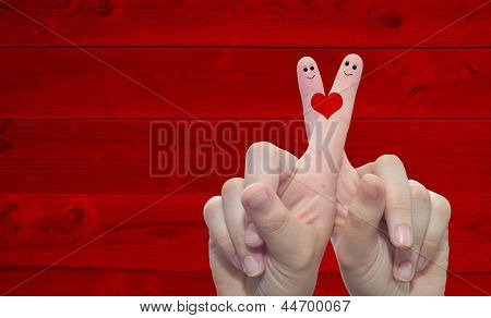 Concept or conceptual human or female hands with two fingers painted with a red heart over a old vintage wood background for valentine,romantic,love,couple,young,family or wedding