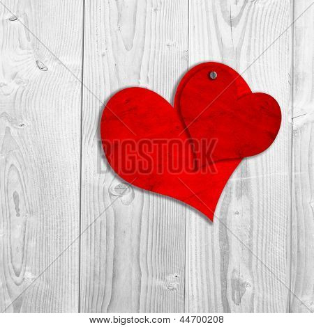 Concept or conceptual two red old paper vintage hearts nailed on white wood or wooden background, metaphor to valentine,romantic,romance,holiday,celebration,gift,card,passion,wedding,message or happy