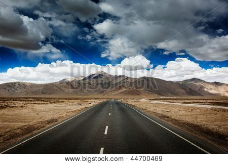 Travel forward concept background - road on plains in Himalayas with mountains and dramatic clouds. Manali-Leh road, Ladakh, Jammu and Kashmir, India