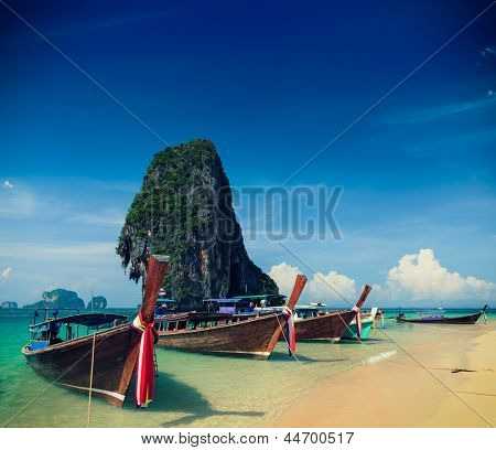 Holiday vacation concept background - Long tail boat on tropical beach with limestone rock, Krabi, Thailand. Cross process version