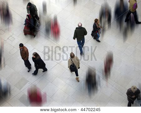 Shoppers in mall combined with other blurred shoppers.
