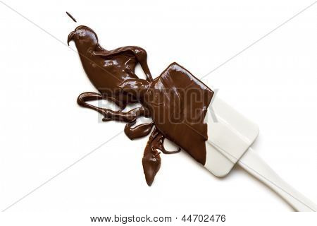 Melted chocolate splashing from a spatula, isolated on white background.