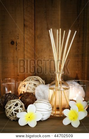 Aromatherapy spa still life with candles, plumeria and towel.