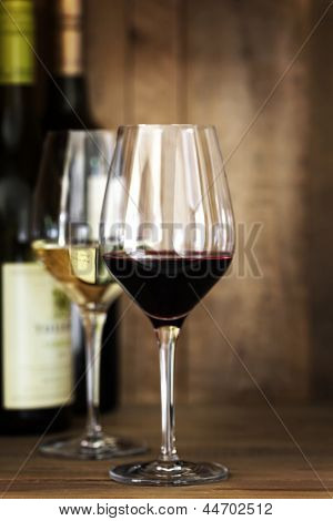 Red and white wine glasses and bottles, over oak background.