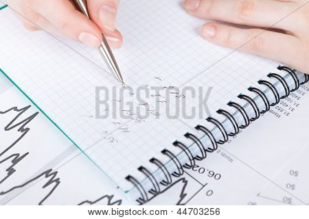Close up of hand making notes in the notebook lying on the diagrams