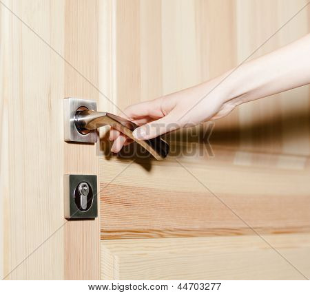 Close up of hand opening the door with door handle